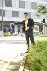 Jovem asiático bem sucedido homem de negócios pegar táxi — Fotografia de Stock