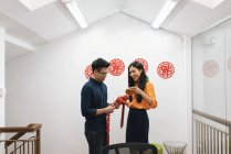 Young happy asian couple celebrating Chinese New Year together and decorating home — Stock Photo