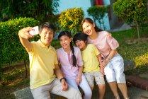 Семья фотографирует вместе на смартфоне — стоковое фото