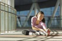 Una giovane donna asiatica si allunga prima del suo allenamento quotidiano a Singapores . — Foto stock