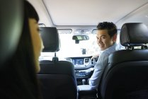Driver smiling at his passenger in the backseat — Stock Photo