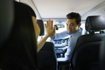 Young male driver giving his female passenger a High-five — Stock Photo