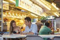 Щасливі молоді азіатські пари сидять разом у вуличних кафе — стокове фото