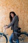Side view of young asian woman with bicycle — Stock Photo