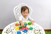 Joven poco asiático niño chica jugando con educativo juguetes - foto de stock