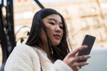Молодая китаянка пользуется смартфоном в Барселоне — стоковое фото