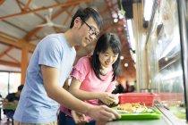 Jeune couple asiatique ensemble, manger de la nourriture dans le café de rue — Photo de stock