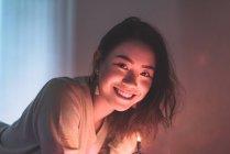 Mujer asiática joven relajante en casa con la guirnalda de la Navidad - foto de stock