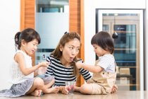 Woman enjoying a healthy snack time with her children. — Stock Photo