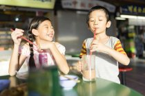 Young asian children drink with drinking straws — Stock Photo