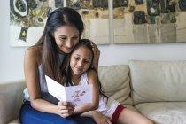 Молодая азиатская мать с симпатичной дочерью сидит дома и смотрит на шаблон — стоковое фото