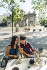 Japanese and Chinese female tourists having coffee in terrace close to Puerta de Alcala in Madrid, Spain. — Stock Photo