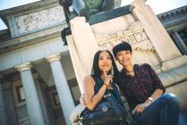 Asian female tourists sitting outside a Museum — Stock Photo