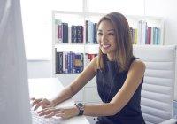Молодая азиатская деловая женщина, работающая с компьютером в современном офисе — стоковое фото