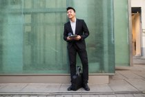 Uomo d'affari cinese con un tablet in strada — Foto stock