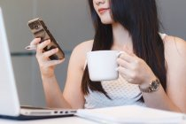 Young Woman Checking Her Phone With Coffee In Hand In Modern Office — Stock Photo