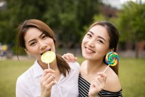 Teen asians girlfriends with candy having fun in the park — Stock Photo