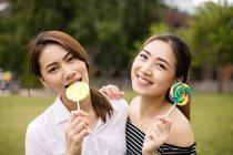 Adolescents asiatiques copines avec des bonbons s'amuser dans le parc — Photo de stock