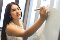 Young Woman Writing On The Whiteboard In Modern Office — Stock Photo