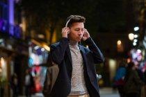 Jeune Chinois décontracté avec écouteurs suspendus dans les rues de Madrid la nuit, Espagne — Photo de stock
