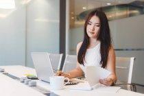 Jeune femme occupée à travailler sur son ordinateur portable dans le bureau moderne — Photo de stock