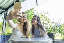 Young attractive asian women taking selfie in cafe — Stock Photo