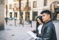 Young couple looking at a map in Barcelona, spain — Stock Photo