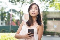 Прелестная азиатская девушка с телефоном на улице — стоковое фото