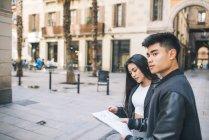 Молода пара, дивлячись на карту в Барселоні, Іспанія — стокове фото