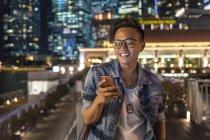 Giovane uomo giocare con il suo smartphone in città — Foto stock
