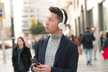 Casual young chinese man using phone and headphones in the street — Stock Photo