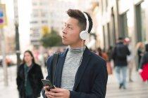 Hombre chino joven casual usando teléfono y auriculares en la calle - foto de stock