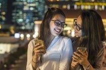 Due giovani signore con i loro smartphone in città urbana — Foto stock