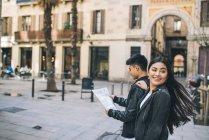 Junges paar schaut auf eine karte in barcelona, spanien — Stockfoto