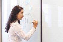 Jeune femme écrivant sur le tableau blanc dans le bureau moderne — Photo de stock