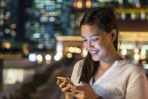 Молодая красивая азиатская женщина с помощью смартфона на открытом воздухе — стоковое фото