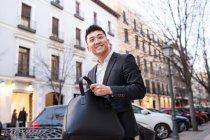 Retrato de un alegre empresario chino en la calle - foto de stock