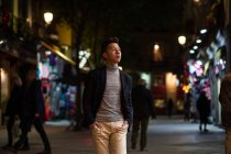 Casual young chinese man hanging around in the streets of Madrid at night, Spain — Stock Photo