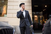 Uomo d'affari cinese che parla al telefono per strada accanto a un negozio di lusso in Serrano Street, Madrid, Spagna — Foto stock