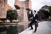 Empresario chino tomando una foto con teléfono en la calle, España - foto de stock