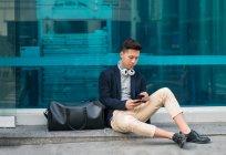 Casual jeune homme chinois assis dans la rue en utilisant le téléphone — Photo de stock