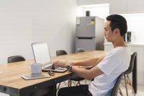 Hombre joven que trabaja con su ordenador portátil en el entorno de inicio - foto de stock