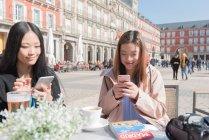 Donne asiatiche in un caffè con smartphone a Madrid, Spagna — Foto stock