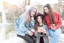 Amigos navegando telefone no Retiro Park Madrid junto ao lago, Espanha — Fotografia de Stock