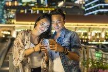 Giovane coppia giocare con lo smartphone in città urbana — Foto stock