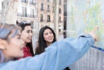 Trois femmes en Espagne en regardant la carte du Conseil — Photo de stock