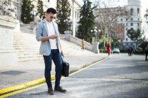 Китайський бізнесмен текстові повідомлення на телефон на вулиці в Мадриді, Іспанія — стокове фото