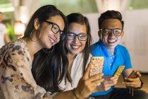 Un gruppo di amici che giocano con i loro smartphone . — Foto stock