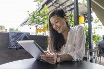Молодая красивая азиатская женщина с помощью планшета — стоковое фото