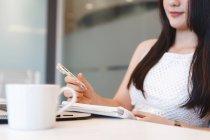 Jeune femme prenant des notes dans le bureau moderne — Photo de stock